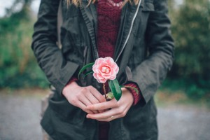 Donna tiene in mano un fiore