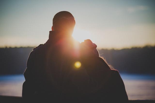 Coppia abbracciata guarda il tramonto